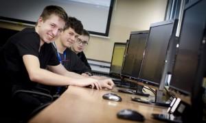 Zdjęcie prezentujące kierunek technik informatyk. Przedstawia trzech uśmiechających się młodych chłopaków siedzących przedkomputerami.