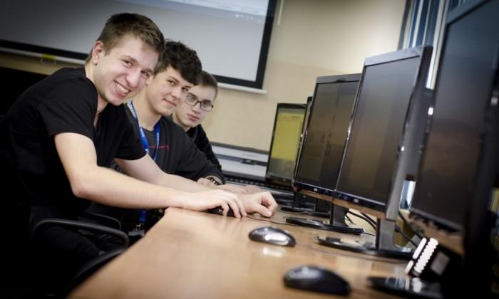 Zdjęcie prezentujące kierunek technik informatyk. Przedstawia trzech uśmiechających się młodych chłopaków siedzących przed komputerami.