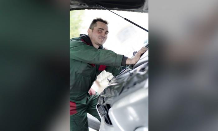 Zdjęcie przedstawia mechanika zawodowego pochylającego się nad otwartą maską samochodu.