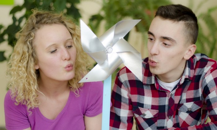 Zdjęcie przedstawia dziewczynę (z lewej) i chłopaka (z prawej). Pośrodku zdjęcia znajduje się papierowy wiatrak, w którego stronę obydwoje dmuchają.