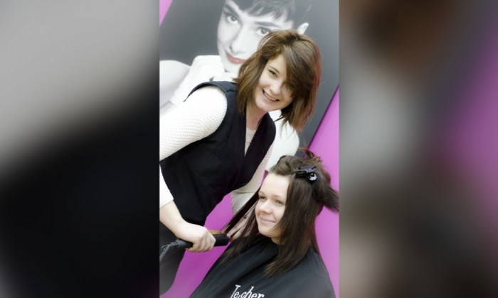 Zdjęcie prezentujące kierunek fryzjerski w zasadniczej szkole zawodowej. Przedstawia dwie uśmiechające się młode dziewczyny. Jedna z nich jest fryzjerką, druga klientką.