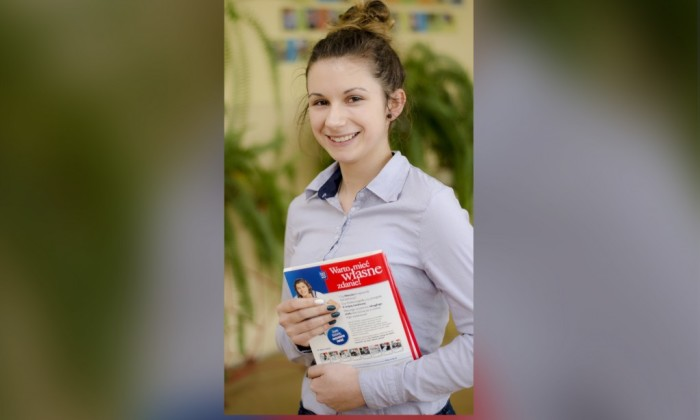Zdjęcie przedstawia uśmiechającą się, młodą dziewczynę ubraną w strój biznesowy.i trzymającą książkę pod tytułem Warto mieć własne zdanie.