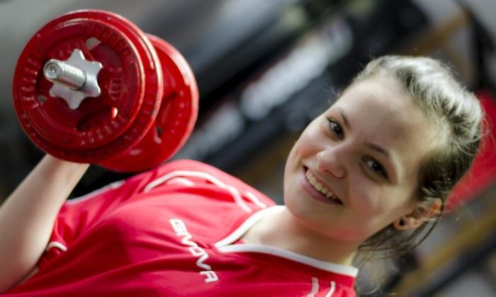 Zdjęcie przedstawia uśmiechającą się młodą dziewczynę w stroju sportowym podnoszącą hantle na szkolnej siłowni
