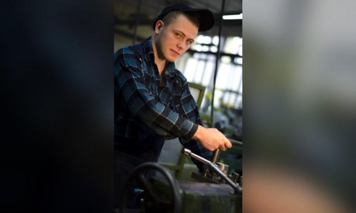 Zdjęcie przedstawia młodego chłopaka w stroju roboczym będącego na warsztatach szkolnych.