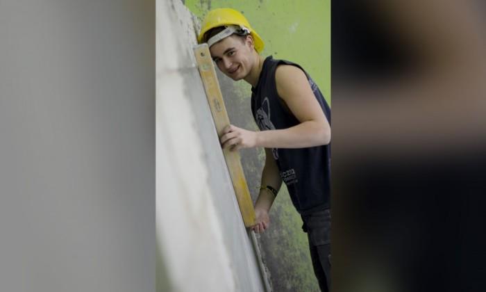 Zdjęcie prezentuje kierunek technik budownictwa. Zdjęcie przedstawia uśmiechającego się młodego chłopaka w kasku. Trzyma on poziomicę murarską przy ścianie.