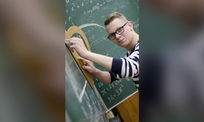 Zdjęcie przedstawia lekko uśmiechniętego młodego chłopaka przy tablicy ze wzorami matematycznymi. Trzyma on w ręce duży, drewniany kątomierz.