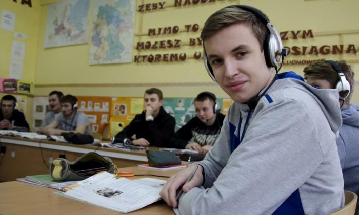 Zdjęcie przedstawia grupę chłopaków, z czego obraz skoncentrowany jest na jednym z nich, który patrzy wprost na obiektyw aparatu. Chłopacy mają na głowie słuchawki z mikrofonami do nauki języków obcych.