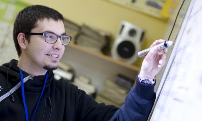 Zdjęcie przedstawia uśmiechniętego chłopaka trzymającego w ręce specjalny pisak-wskaźnik. Stoi on przed tablicą interaktywną.